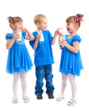Smiling children with a glass of milk. Little girls-twins and boy are drinking milk of glasses in their hands and are laughing on white background Royalty Free Stock Photography