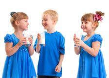 Smiling children with a glass of milk. Little girls-twins and boy are drinking milk of glasses in their hands and are laughing on white background Stock Photography