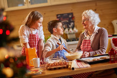 Smiling children and grandmother preparing Xmas cookies. Family time Stock Photo