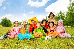 Smiling children in Halloween costumes together. Smiling children in Halloween costumes sitting on the grass of the field and look royalty free stock photography
