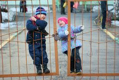 Smiling children have fun swinging on the gate. In the spring Stock Images