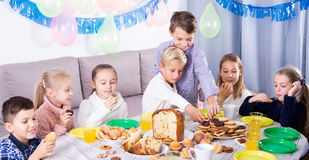 Smiling children having dinner to birthday Royalty Free Stock Photo