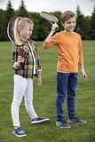 Smiling children holding badminton racquets while standing on green grass. Adorable smiling children holding badminton racquets while standing on green grass stock photos