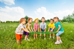 Smiling children holding one hoop together Stock Photos