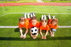 Smiling children lay on grass with golden goblet Royalty Free Stock Images