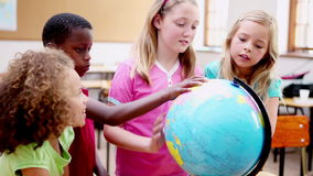 Smiling children looking at a globe Stock Photography