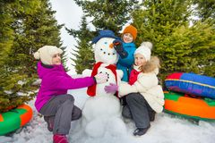 Smiling children make cute snowman in forest. Smiling children make cute snowman with boy holding his carrot nose during beautiful winter day in the forest royalty free stock photo