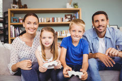 Smiling children playing video games with parents Royalty Free Stock Photos