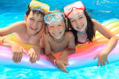Smiling Children in Pool. Smiling children wearing snorkel goggles and floating on a colorful raft stock photo