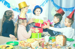 Smiling children presenting gifts to girl birthday Royalty Free Stock Image