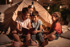 Smiling children reading book at home. Multicultural group of smiling children reading book at home Stock Image