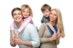 Smiling children riding piggyback on parents Royalty Free Stock Image