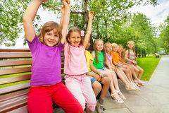 Smiling children sit in row on the bench. And two of them hold arms up straight in the air stock image