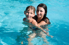 Smiling children in the swimming pool. Of water park in sunny summer day Royalty Free Stock Photos