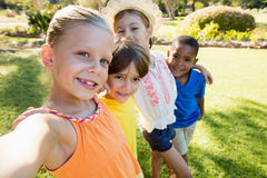 Smiling children taking selfie. In the park royalty free stock photography