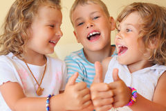 Smiling children three together shows ok gesture Royalty Free Stock Image