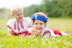 Smiling children in ukrainian folk clothes. On grass meadow Stock Images