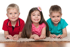 Smiling children on the white carpet Royalty Free Stock Photography