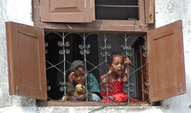 Smiling children in window Stock Photography