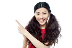 Smiling chinese girl pointing away Royalty Free Stock Image