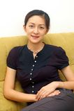 Smiling Chinese Lady. Beautiful Asian Chinese lady smiling and siting on sofa at home Stock Images