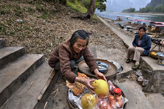 Smiling Chinese woman trades fruit on steps leading to pier. Stock Photos