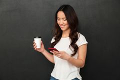 Smiling chinese woman typing text message or scrolling social ne. Twork on smartphone while drinking takeaway coffee over gray background stock photography
