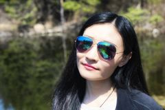 Smiling Chinese woman wearing sunglasses springtime. A chinese woman wearing blue sunglasses at Topsmead state forest in Litchfield Connecticut on a spring day royalty free stock photography