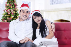 Smiling christmas couple in santa hats Stock Image