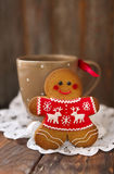Smiling christmas gingerbread men on wooden background. Smiling christmas gingerbread men and tea cup on wooden background Royalty Free Stock Photo