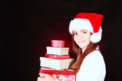 Smiling christmas girl holding presents over dark Royalty Free Stock Photos