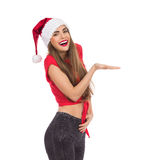 Smiling christmas girl presenting product Royalty Free Stock Photo