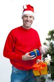 Smiling christmas man wearing santa hat at the Christmas tree Stock Image