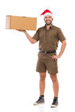 Smiling Christmas Messenger Is Holding Carton Box In One Hand. Smiling delivery man in khaki uniform and santa claus hat is standing and holding carton box in Stock Photos