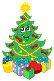 Smiling Christmas tree with gifts Stock Photo
