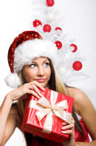 Smiling Christmas woman. Isolated on white background with a gift and a tree Stock Photography