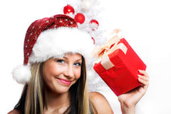 Smiling Christmas woman. Isolated on white background with a gift and a tree Stock Photos