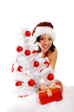 Smiling Christmas woman. Isolated on white background with a gift and a tree Stock Photo