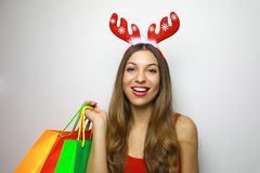 Smiling christmas woman with reindeer horns and shopping bags looking at the camera on white background. Copy space royalty free stock photos