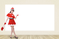 Smiling Christmas woman show something Stock Photo