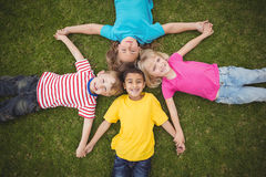Smiling classmates lying in grass and holding hands Stock Photo