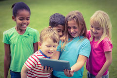 Smiling classmates using tablet together Royalty Free Stock Photos