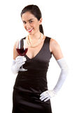 Smiling Classy Woman Holding a Glass of Red Wine. A beautiful smiling woman in a classy dress is holding a glass of red wine royalty free stock photos