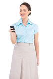 Smiling classy young businesswoman sending text message Royalty Free Stock Photos