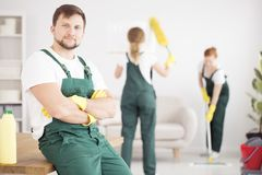 Smiling cleaner in green overalls. And yellow gloves in the flat cleaned by a cleaning crew stock photography
