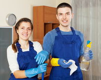 Smiling cleaners team cleaning floor. In room stock photography