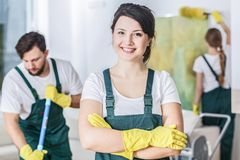 Smiling cleaning lady. In a green uniform and yellow rubber gloves at work stock photo