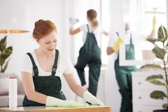Smiling cleaning lady wiping table. Smiling cleaning lady wiping the table. Home cleaning service business royalty free stock images