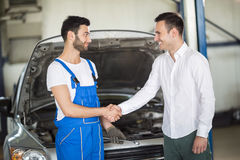 Smiling client and mechanic shaking hands Royalty Free Stock Photos