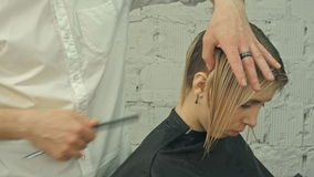 Smiling client sitting in a hair salon while hairdresser is combing her hair. Focus on client stock footage